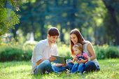 picture of happy day  - Happy family of three people resting in a city park with a tablet in hands - JPG
