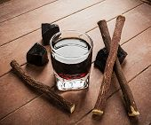 foto of licorice  - Licorice liqueur with pure blocks and roots on wooden table - JPG