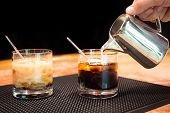 stock photo of marsala  - Preparation of white russian cocktails on the bar counter on rubber mat - JPG