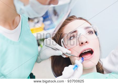 Young woman patient with dental cases during treatment in dentist chair in dental clinic