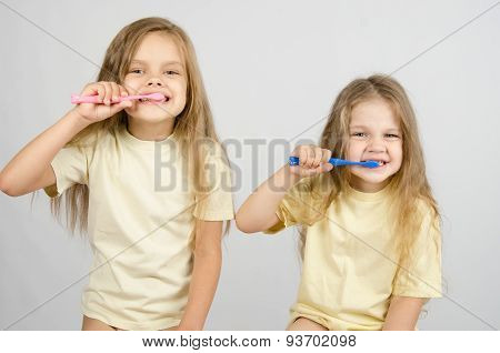 Two Sisters Brushing Their Teeth