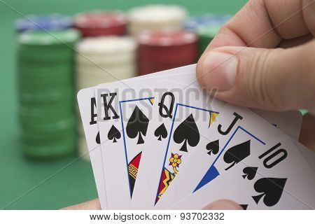 Poker Player Holding 10 To King Spade Straight Flush Of Pokers, A Spade  Is Coming