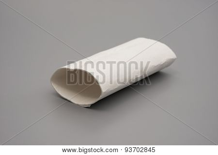 Smashed Toilet Roll With The Last Bit Of Tissue On Grey