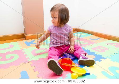 Adorable baby girl playing on floor