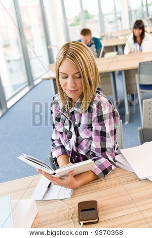Happy Female Student With Book In Classroom