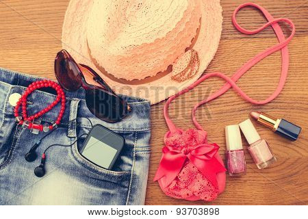 Summer women's accessories: sunglasses, beads, denim shorts, mobile phone, headphones, a sun hat,