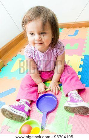 Adorable baby girl playing on floor mats