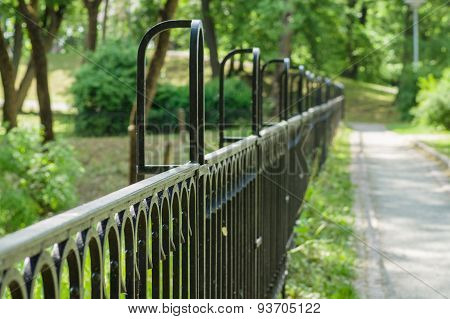 Vanishing Decorative Wrought Iron Fence In Sunny Park