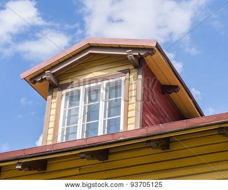 Mansard Window In Wooden House Under Blue Sky