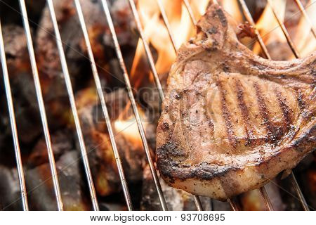 Grilled Pork Steaks Over Flames On The Grill.