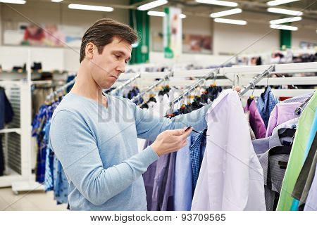 Surprised Man Looking At Price Tag Of Goods