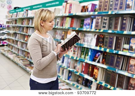 Woman Chooses Book In Store
