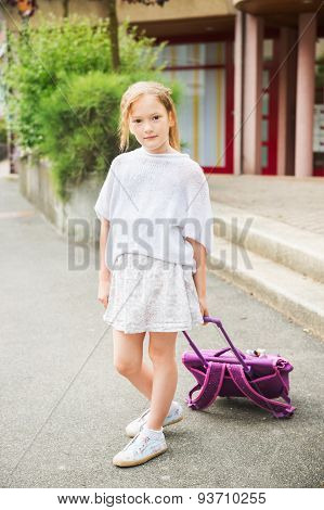 Cute little girl of 7 years girl walking to school, carry backpack with wheels