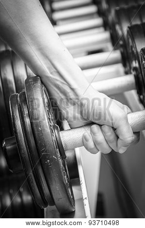 Hand holding dumbbell.Close up.Muscular arm in the gym