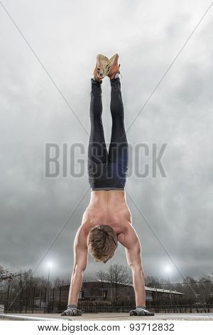 Handstand in front of grey sky