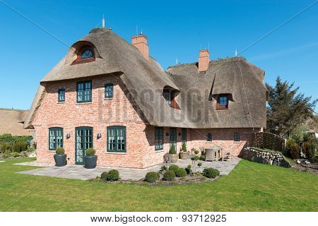 House with thatched roof in front of blue sky