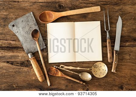 Empty notebook or cookbook and vintage kitchen utensils on wooden table
