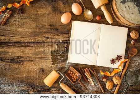 Baking concept background with cookbook, ingredients and utensils for Christmas cookies