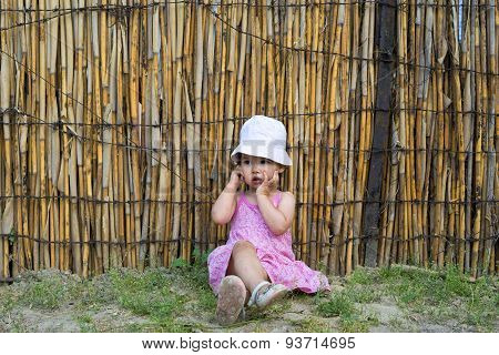 Upset Little Girl Covering Her Mouth With Palms And Looking Aside