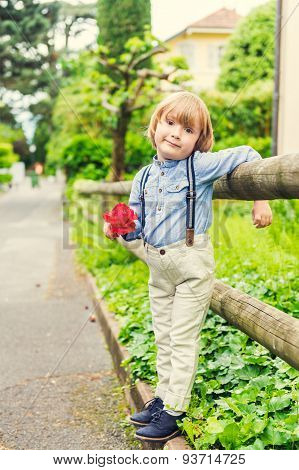 Outdoor portrait of a cute little boy wearing trousers with suspenders, holding red rose
