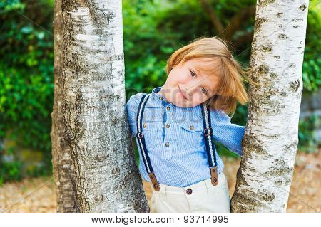 Close up portrait of adorable little blond boy, wearing pants with suspenders
