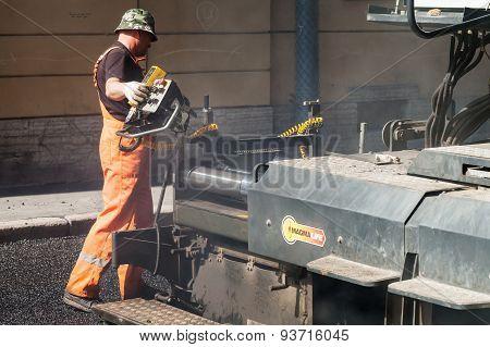 Operator Walks Near Paver, Men At Work