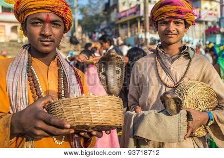 VARANASI, INDIA - 23 FEBRUARY 2015: Two Indian boys dressed up in religious clothes hold cobras in baskets.
