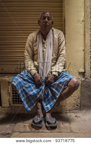 VARANASI, INDIA - 20 FEBRUARY 2015: Indian man sitting next to closed store wearing shirt, scarf, lungi and slippers.