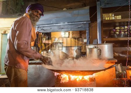 VARANASI, INDIA - 21 FEBRUARY 2015: Street vendor cooks meal in big pan on coal oven at night.