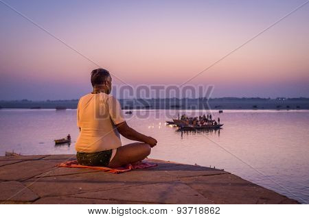 VARANASI, INDIA - 23 FEBRUARY 2015: Indian man meditates next to sacred Ganges river on  Varanasi ghat while people perform puja on boats in background.