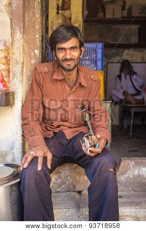 VARANASI, INDIA - 21 FEBRUARY 2015: An electrician rests in front of shop with electronic part in hand.