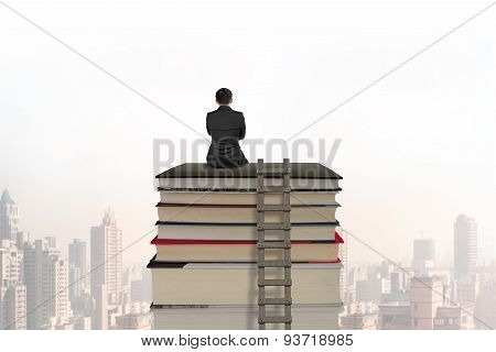Businessman Sitting On Stack Of Books With Wooden Ladder
