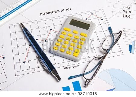 Close Up Of Business Plan With Graphs, Charts, Glasses, Pen And Calculator