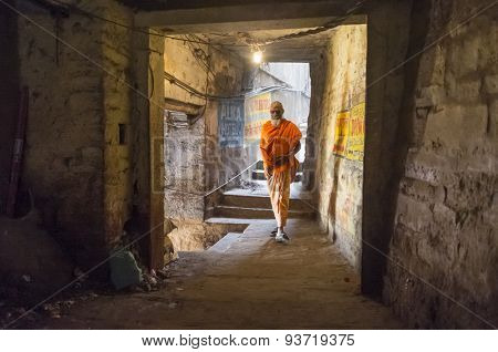 VARANASI, INDIA - 20 FEBRUARY 2015: A sadhu walks through a passage.  In Hinduism, a sadhu is a religious ascetic or holy person.