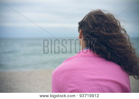 Young Woman With Curly Hair Sitting Alone On The Beach In Cloudy Weather