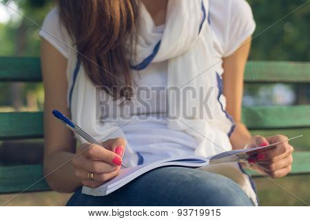 Young Woman Student Sitting On A Bench In The Park