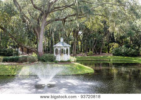 Fountain In Lake By Oak Tree And Gazebo