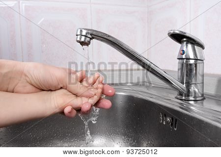 A Women's Hand Helps Child To Washes His Hands