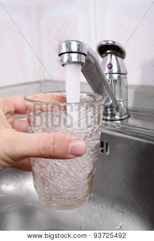 Hand Pours Water Into A Glass From Kitchen Faucet