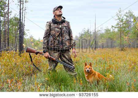 Hunter With A Gun And A Dog On The Swamp