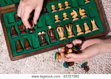 Hands Putting The Chess Pieces In Box