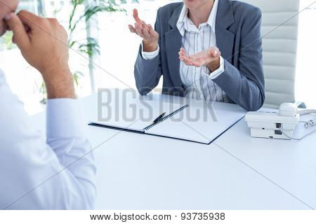 Businesswoman conducting an interview with businessman in an office