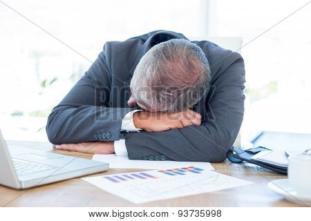 Tired businessman resting on desk in his office