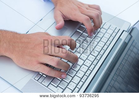 Close up plan of a businessman typing on his laptop