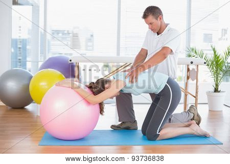 Trainer working with woman on exercise ball in fitness studio