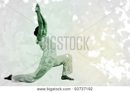 Content brunette in white doing tai chi against detail shot of bright green leaves