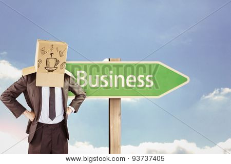 Anonymous businessman with hands on hips against business road sign