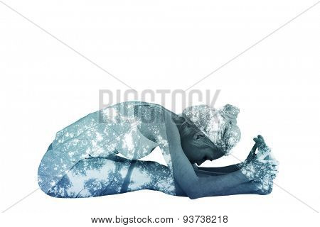 Toned woman doing the paschimottanasana pose against low angle view of tall trees