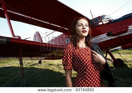 pin-up lady stands against plane in dress