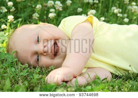 Laughing Newborn Baby Laying In Grass Outside